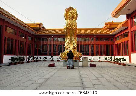 An Asian woman praying to Buddha