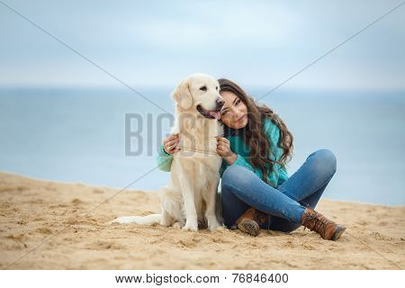 Young woman with her dog on the beach.