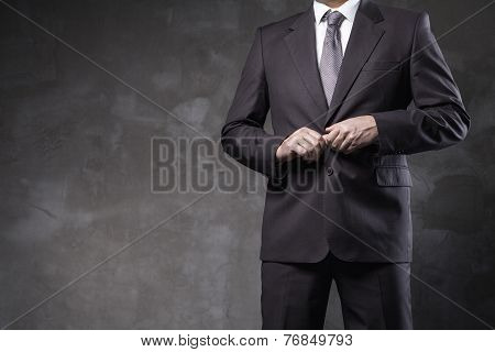 Man poses in his suit front of grunge wall
