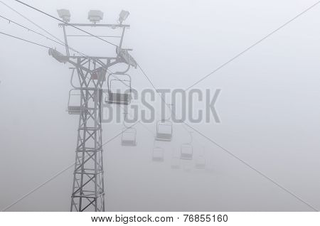 Chairlift vanishing into fog