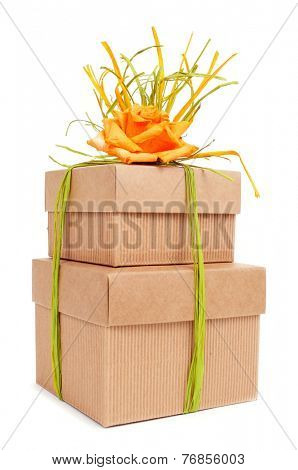 some gift boxes tied with natural raffia of different colors and topped with a flower on a white background