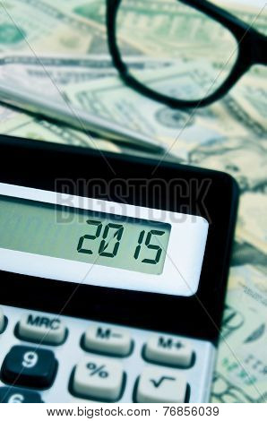 the number 2015, as the new year, in the display of a calculator on a pile of US dollar