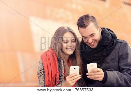 A picture of a young couple sitting on a bench and using smartphones on an autumn day