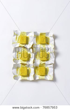 six cubes of bouillon in the paper wrappers