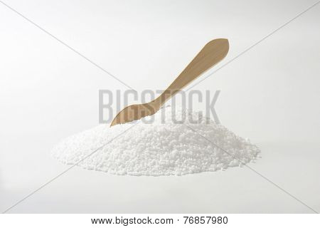 side view of salt heap with immersed wooden spoon