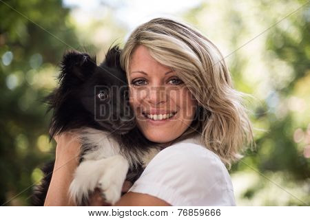 Portrait of a woman with her cute dog at the park