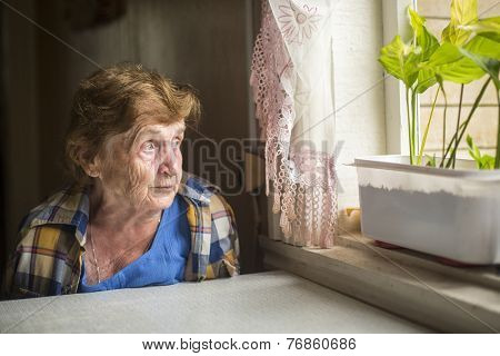 Old woman sitting alone near the window in his house. Loneliness in old age.
