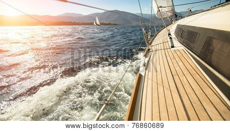 Yacht sailing towards the sunset. Sailing. Luxury yachts.