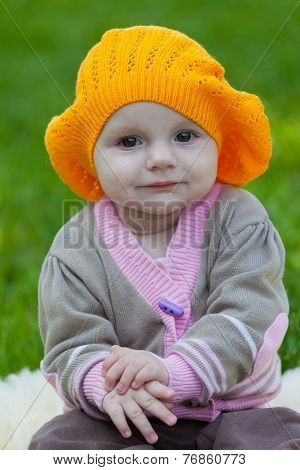 Little girl in an orange beret against a green grass