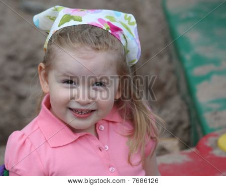 Cute Girl Smiling In Sandbox With A Scarf On Head