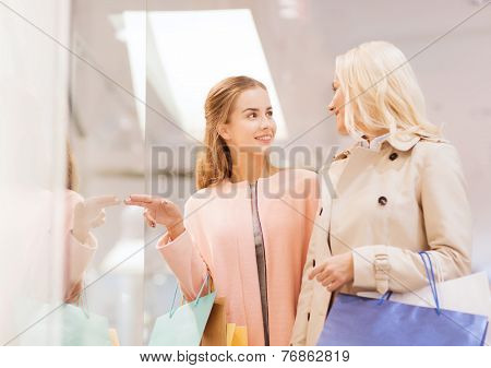 sale, consumerism and people concept - happy young women with shopping bags pointing finger to window in mall