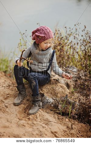 Cute child girl playing with stick in knitted hat and sweater in autumn day