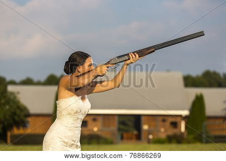 A bride in a wedding dress shooting a shotgun