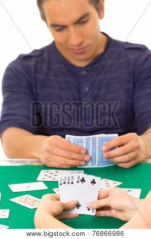 young man playing cards cuarenta traditional Ecuadorian game