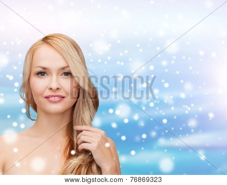 heath, people, haircare and beauty concept - beautiful young woman with bare shoulders touching her hair over blue sky, snow and clouds background