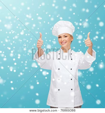 christmas, cooking, profession, gesture and people concept - smiling female chef showing thumps up over blue snowy background