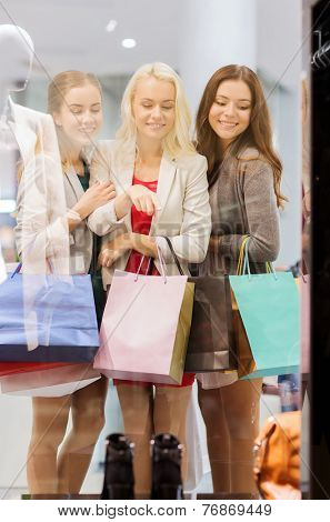 sale, consumerism and people concept - happy young women with shopping bags pointing finger to shop window in mall