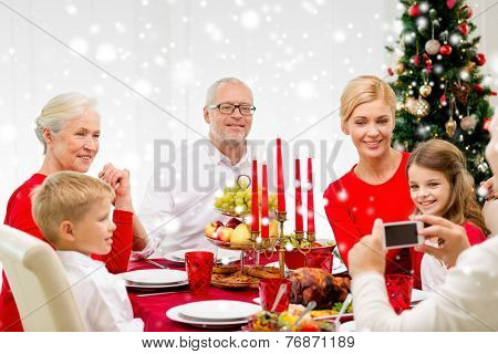 family, holidays, generation, christmas and people concept - smiling family having dinner and making photo with camera at home