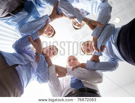 business, people and teamwork concept - smiling group of businesspeople standing in circle and holding to each other hands