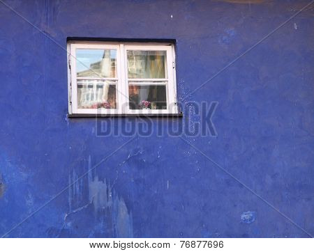 Small od window in the old blue building.