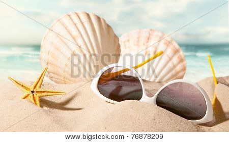 closeup of shell starfish and sunglasses on sunny beach with blurry sea in the background