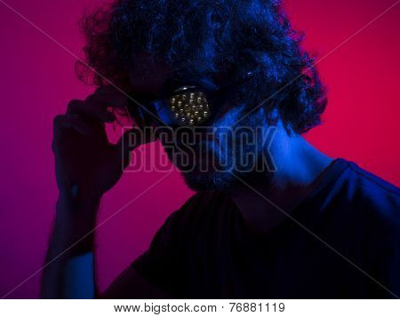 Cyborg man in shadows with red backdrop and blue key light, with bionic led eye