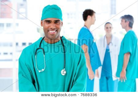 Afro Male Doctor Looking At The Camera While His Medical Partners Talking Together