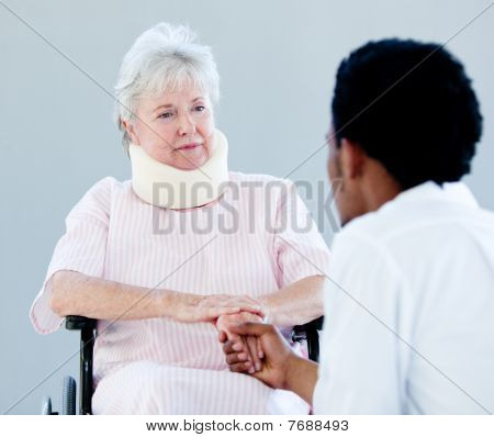 Senior Woman Sitting On A Wheelchair With A Neck Brace Talking With Her Doctor