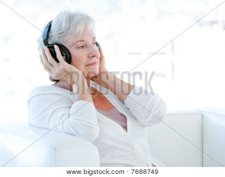 Charming Senior Woman Listening Music With Headphones