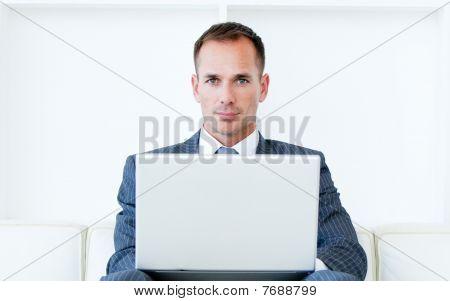 Empresario seguro usando una Laptop sentado en un sofá