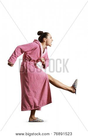 angry housewife in pink dressing gown giving a kick and screaming. isolated on white background