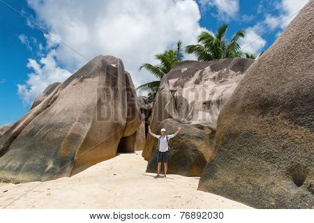 Tourist Posing at Huge Rocks at Anse Source d'Argent in La Digue Island, Seychelles.