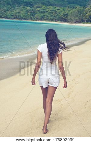 Young Asian woman walking on a tropical beach with her long hair blowing in the wind as she crosses the golden sand of a lush green bay on a hot summer day on her vacation