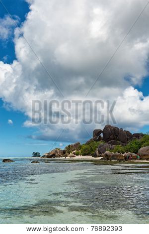 Tropical View of Anse Source d'Argent with Stormy Sky Above Clear Water Lagoon and Large Rocks on the Side.