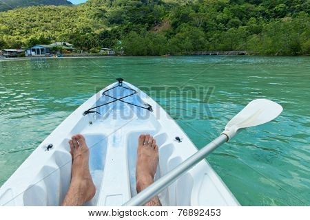 Man canoeing in the Seychelles off the coast of Mahe island near Port Launay, view of his bare feet and paddle in the bows