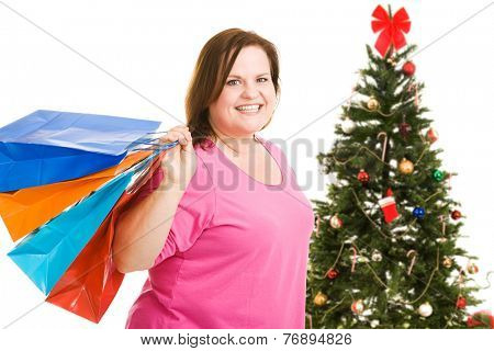 Happy plus sized model holding shopping bags, standing in front of a Christmas tree.  Isolated on white.
