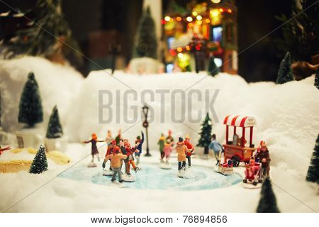 Miniature toys composition of people skating on ice skating rink