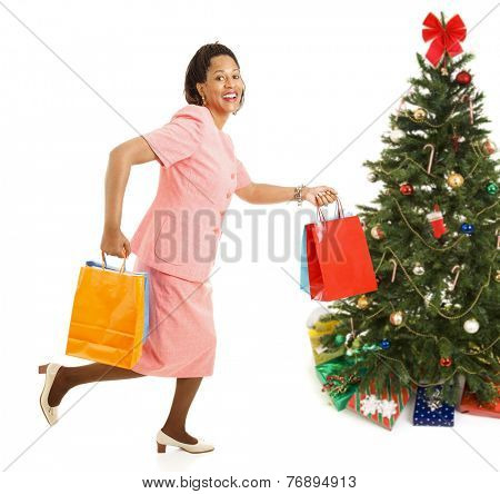 African-american female shopper running from one store to another for bargains on Christmas gifts.  Isolated on white.