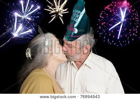 Beautiful senior couple at a New Year's party kisses at the stroke of midnight as the fireworks go off in the background.