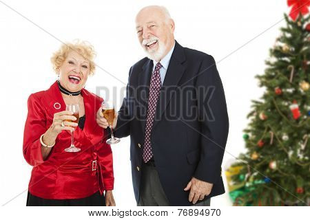 Senior couple laughing and drinking champagne at a Christmas party.  Isolated on white.