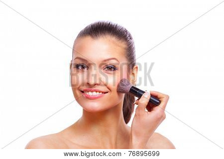 Beautiful young woman applying cosmetic paint brush