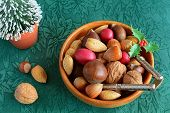 stock photo of pecan tree  - Mixed nuts in the shell for a Christmas treat on green poinsettia background - JPG