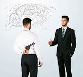 stock photo of backstabbers  - Ruthless businessman hiding a weapon and weaving plan around his head  - JPG