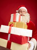 foto of generous  - Generous Santa with pile of Christmas presents - JPG