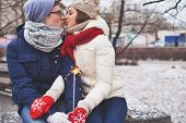 picture of amor  - Amorous couple with Bengal light kissing in winter park - JPG