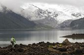 image of trough  - Hiker wading trough rocks near like and stones - JPG