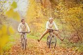 foto of older men  - Active seniors ridding bike in autumn nature. They having fun outdoor.