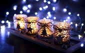 stock photo of christmas wreath  - Advent four candles decorated Christmas tree on a background of lights