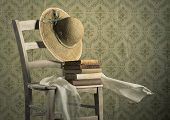 stock photo of vintage antique book  - Stack of ancient books on a chair with straw hat and headscarf vintage wallpaper on background - JPG