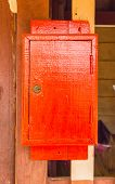stock photo of postbox  - old traditional red wooden postbox on the wall - JPG
